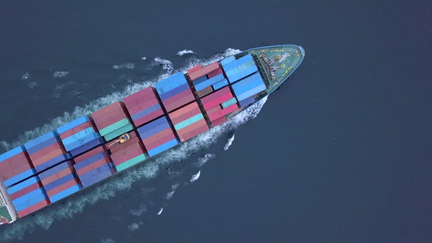 Aerial shot of container ship, Flying over massive container ship filled with multicolored containers moving in the quiet sea. Colorful containers being moved by large international cargo ship