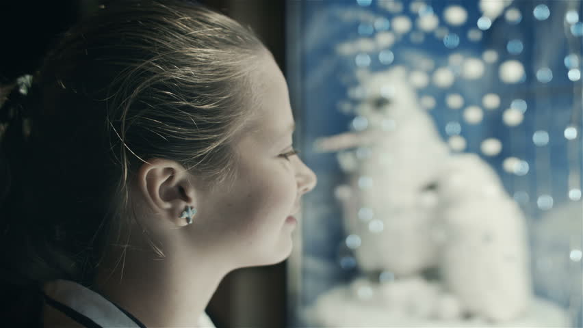 The girl was looking at the new year showcase. Christmas Eve. Dreaming about gift
