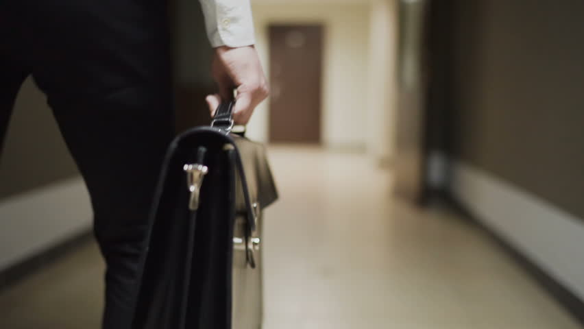 Businessman with briefcase walking across the office building. Slow motion 100 fps