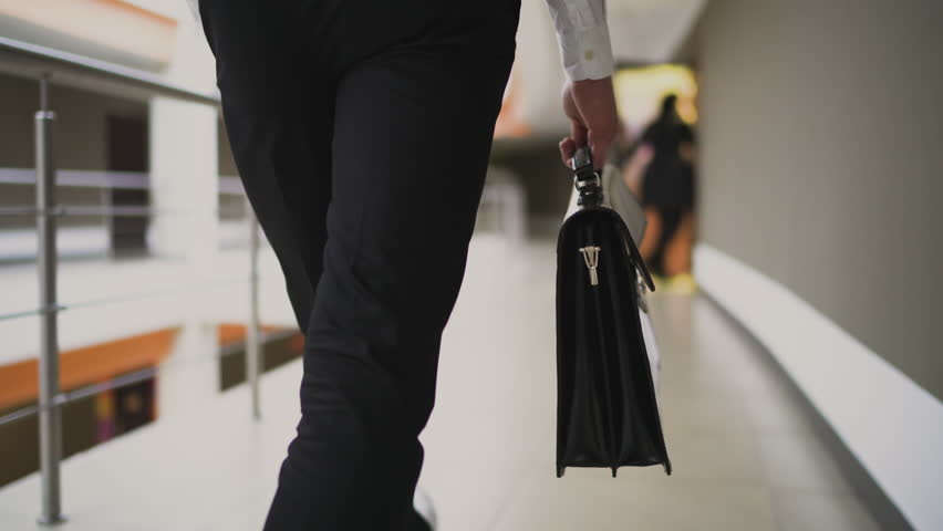 Businessman with briefcase walking across the office building. Close up. 4K Royalty-Free Stock Footage #33511423