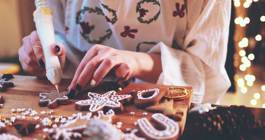 Woman Decorating Baked Gingerbread Christmas Cookies. 4K SLOW MOTION.  Female hands frosting and icing fresh holiday bakery. Festive food, family, Christmas and New Year traditions concept.