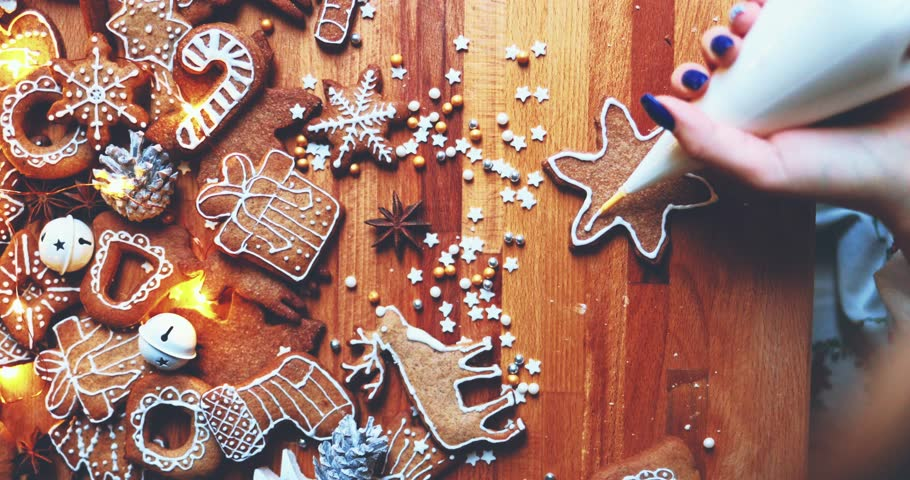 Woman Decorating Baked Gingerbread Christmas Cookies, Top View. 4K SLOW MOTION.  Female hands frosting and icing fresh holiday bakery. Festive food, family, Christmas and New Year traditions concept.