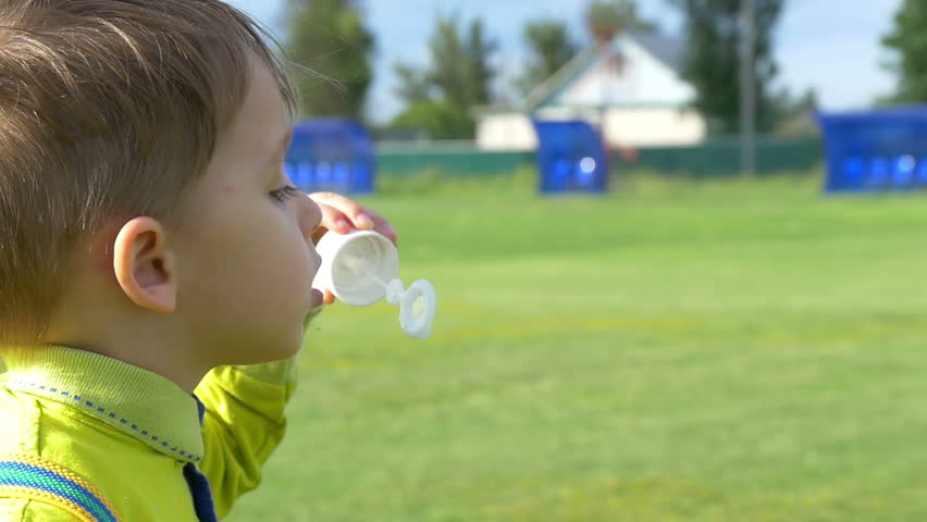 A child boy blowing soap bubbles while on a green lawn in a slow close-up motion. Happy childhood | Shutterstock HD Video #33515308