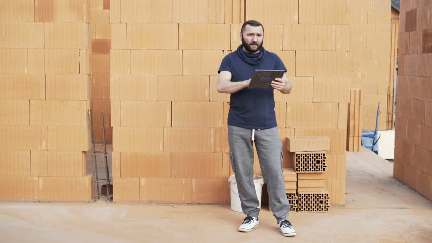 Young male constructor with tablet talking about home to camera at construction site   Shutterstock HD Video #33516544