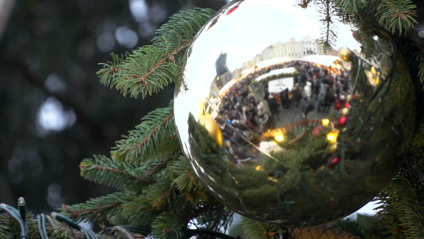 A Ball  Garlands Hang On Christmas Tree and reflect Old Totwn Square market . Close up.  | Shutterstock HD Video #33518140