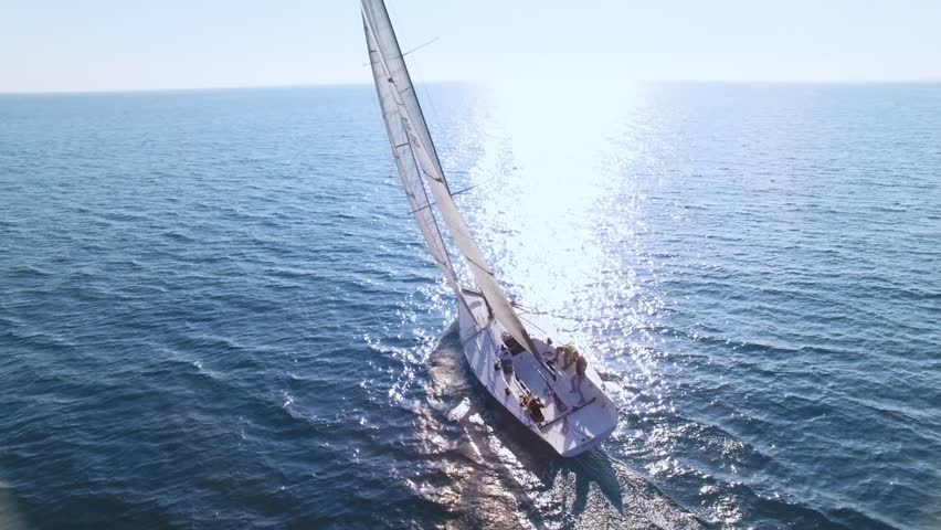 Aerial footage from drone, of professional speed yacht or sailboat leaning to one side, ready to make a maneuvre, wind in mainsail attached to mast, team race or competition, with sun flares | Shutterstock HD Video #33518569