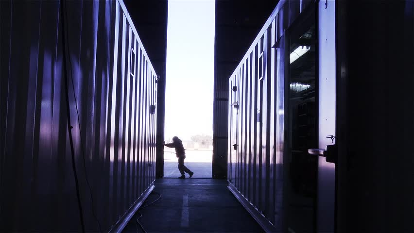 Man Opening the Door of a Container Warehouse. View from Inside.