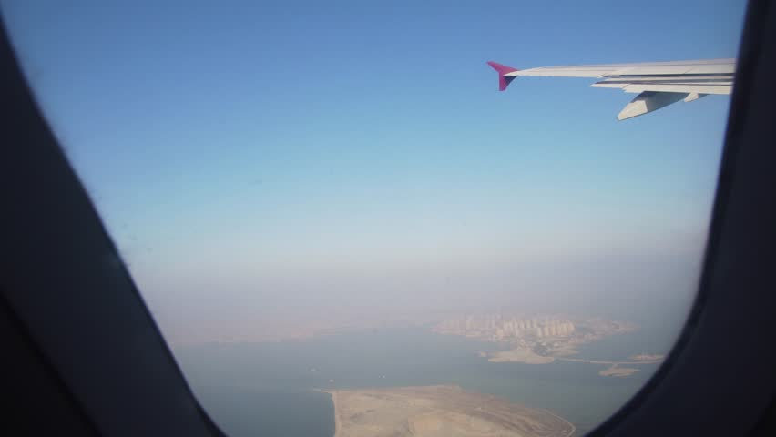 View through an airplane window on the city Qatar. Airplane window view showing wing of a plane flying over city. 4K video, Travel concept. #33552913