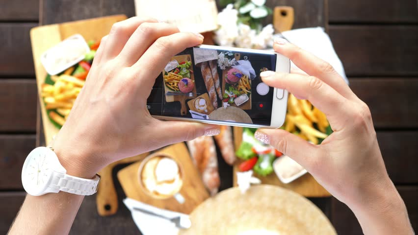 Hands Using Smartphone Taking Photos Of Hipster Flat Lay With Burgers, French Fries, Coffee and French Baguettes. Closeup. 4K.  #33583552