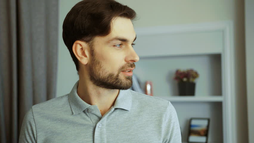 Portrait of young handsome man looking directly to the camera and smiling sincerely in the cozy living room at home. Close up | Shutterstock HD Video #33588229