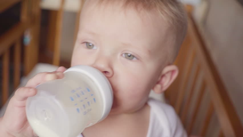 Smiling baby boy standing and drinking milk from a bottle