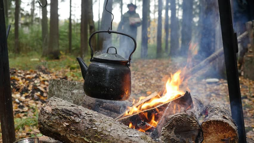 A hiker with firewood and an ax approaches the fire on which kettle is boiling