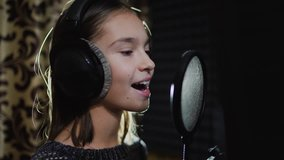 Singer child is training to make music in professional studio. Song production process. Talented kids. Track recording.