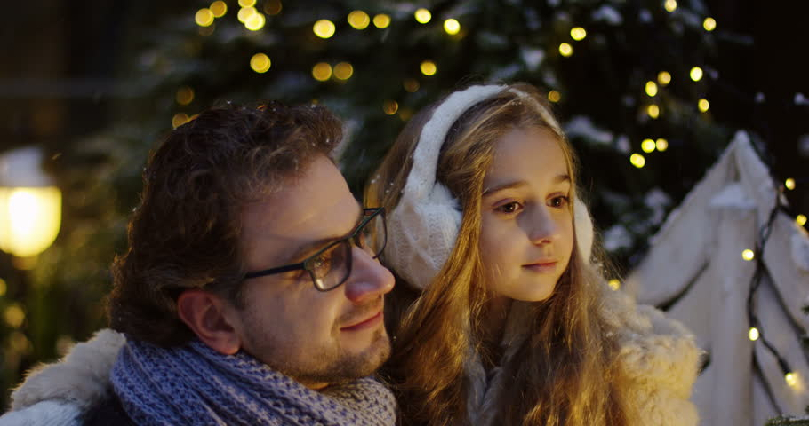 Handsome man in glasses hugging with his pretty daughter, talking and looking fascinated up surrounded by the Christmas decorations on the street in the late evening. Outside. Close up. Portrait shot | Shutterstock HD Video #33628828