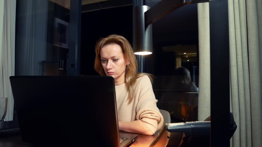 Woman working on a laptop at a table at night in a hotel room.  | Shutterstock HD Video #33632134