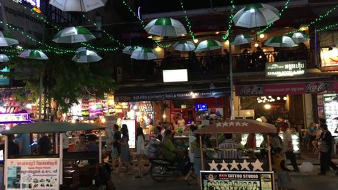 SIEM REAP, CAMBODIA - NOVEMBER 2017: Unidentified tourists walk by tuktuk drivers offering their service at Pub Street at Siem Reap city downtown.