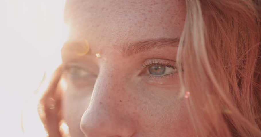 Close-up of redhead woman with green eyes and freckles looking at view in summer