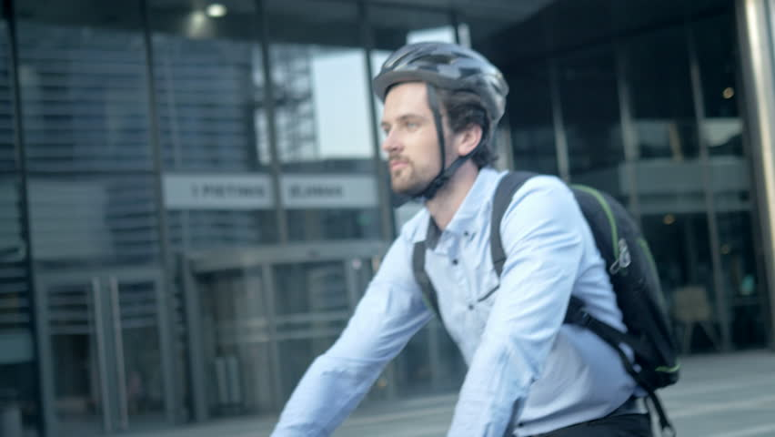 Close-up shot of a handsome commuter cycling to his office. Happy smartly dressed man riding a bike. Active and healthy way of traveling to job. #33634240