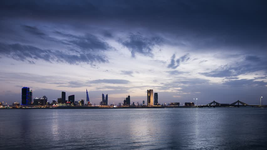 Time-lapse of cloudy sunset and Manama cityscape in blue hour.