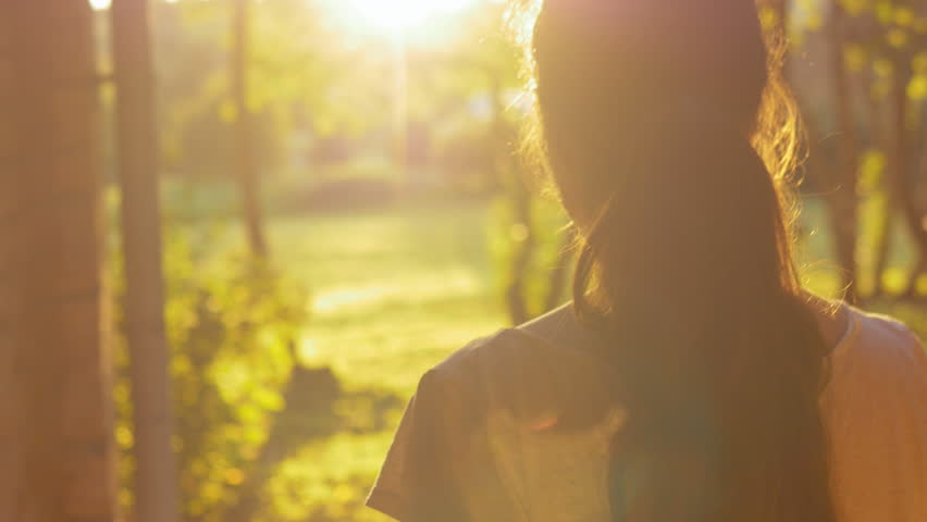 Young woman opening the door and slowly walking outside. Female escaping the city life and enjoying nature and freedom, breathing fresh air outdoors early in the morning. Lens flare.