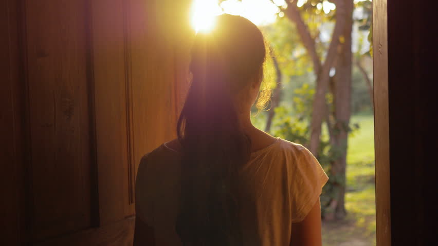 Young woman opening the door and slowly walking outside. Female escaping the city life and enjoying nature and freedom, breathing fresh air outdoors early in the morning. Lens flare. | Shutterstock HD Video #33635608