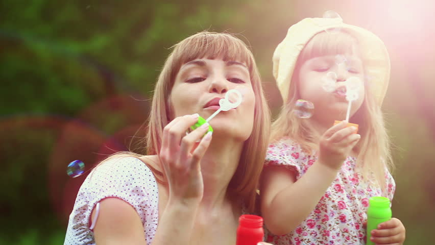 Sunny family blowing air bubbles. Lens flares