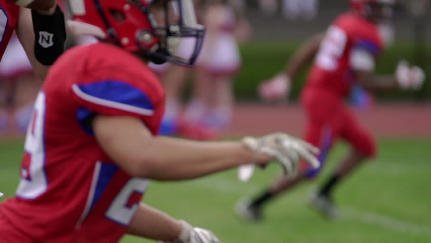 High school quarterback receives snap, in slow motion