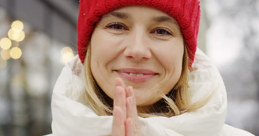 Close up of the attractive middle aged woman in red hat smiling into the camera and warming her hands on the winter white town street. Outdoor. Portrait