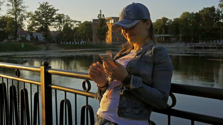 Pretty happy woman using smartphone in city park