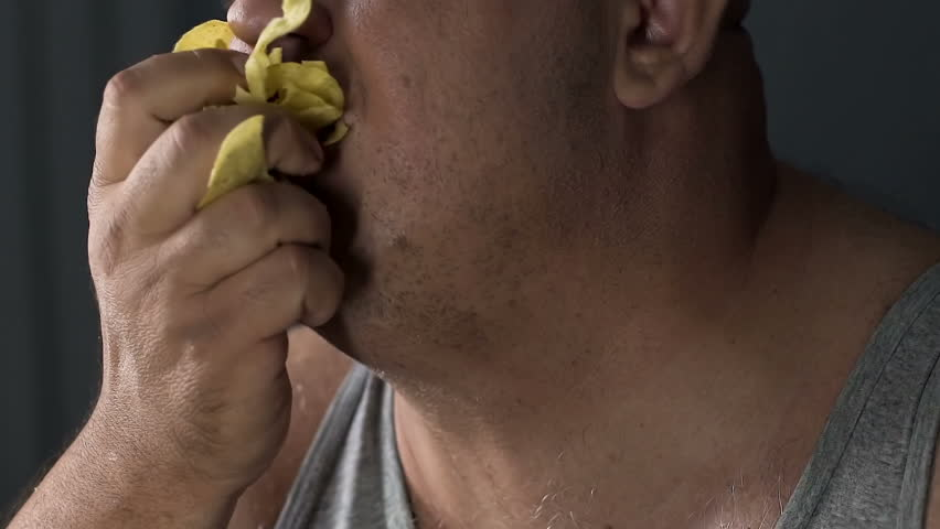 Man eating crisps with appetite, psychological problem, unhealthy food addiction