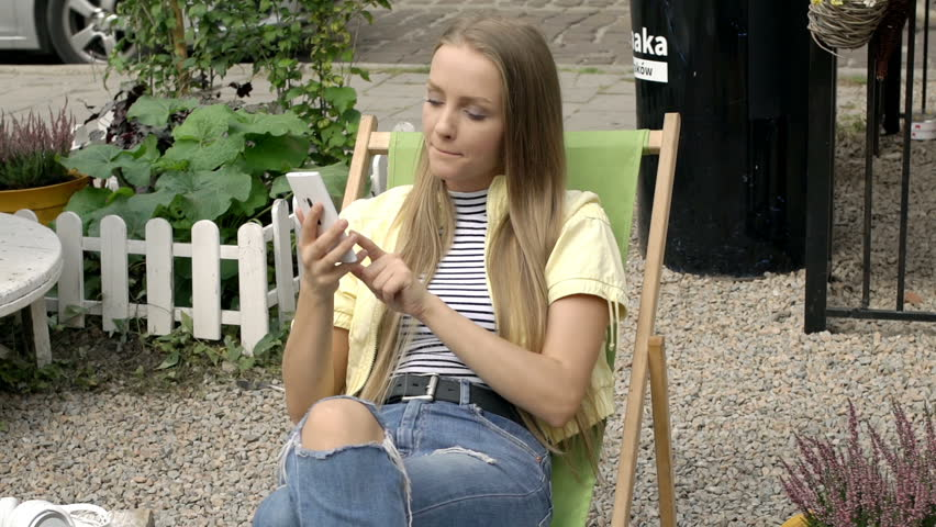 Unhappy girl talking on cellphone while sitting on sunbed and receives bad news