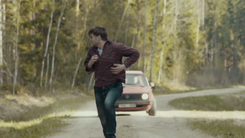 Scared man running in slow motion from the chasing car through the forest road