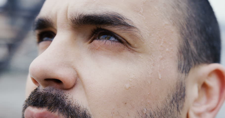 Close up of the attractive man's face with a beard and dark eyes looking in the sky with deep thoughts and turning his head with drops of sweat to the camera with a shrewd look. Motivation for