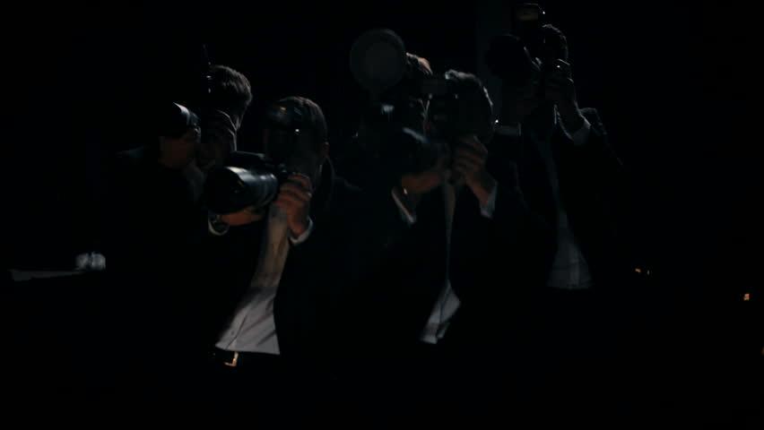Camera flashes group of paparazzi