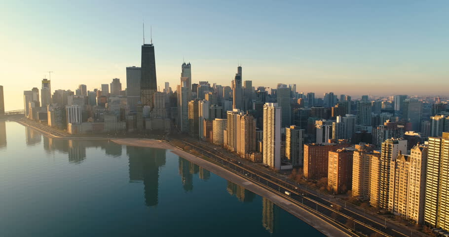 Flying backwards above Chicago Downtown skyline at sunrise. Road by the shore with cars   Shutterstock HD Video #33722446