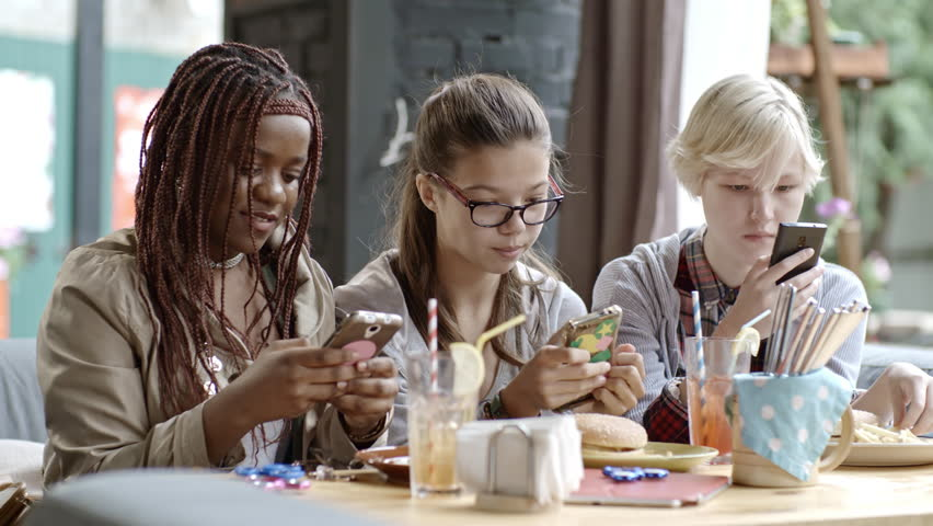 Three teen girls glued to smart phones sitting together at cafe table and eating fast food dinner