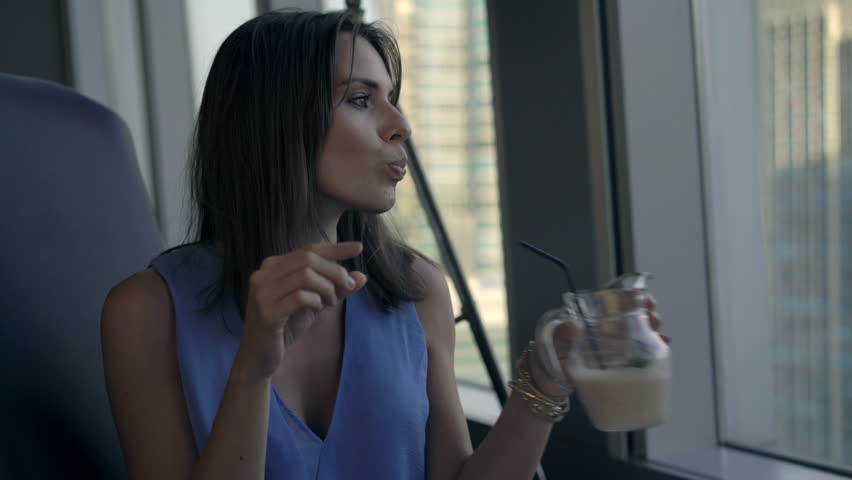 Young woman drinking cocktail sitting by window in cafe  | Shutterstock HD Video #33735169