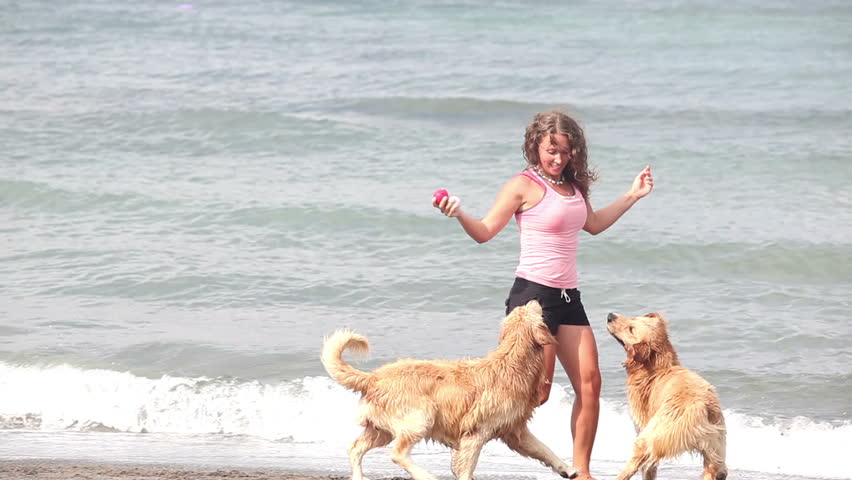 Beautiful happy woman playing with two dogs at beach