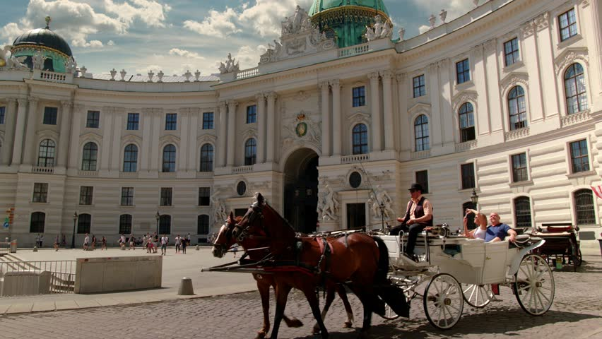 "A viennese Coach, so called ""Fiaker"" passes by at the Michaelerplatz at this wide angle shot of the ""Wiener Hofburg"", Sky is replaced.  Variation without:"