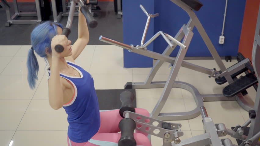 Female athlete doing wide grip pulldowns exercise in gym. Woman sits on seat of iron machine and holds handles with hands and pulls them to chest level, moving body up. Cute person dressed in blue t | Shutterstock HD Video #33742390