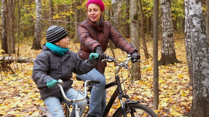 Son speaks with his mother when they sit on bikes and look upward at park | Shutterstock HD Video #3374753