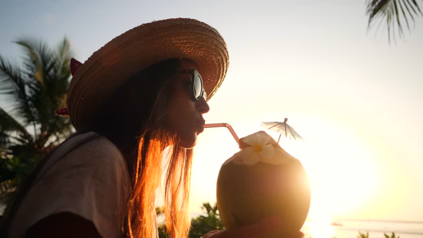 Attractive Young Tourist Hipster Girl Drinking Fresh Thai Coconut Water Cocktail at the Beach Against Beautiful Sunset. 4K, Slowmotion. Phuket, Thailand. Royalty-Free Stock Footage #33769894