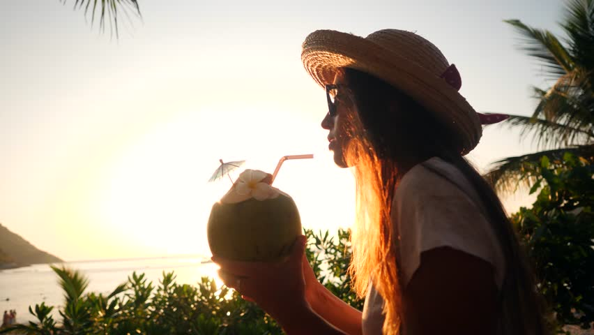 Attractive Young Mixed Race Tourist Girl Drinking Fresh Thai Coconut Water Coctail at Beach Against Beautiful Sunset. 4K, Slowmotion. Phuket, Thailand.