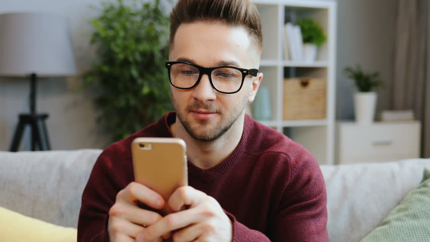 Portrait shot of the attractive man in glasses sitting at home and typing on the black smartphone. Close up. Indoor | Shutterstock HD Video #33770041