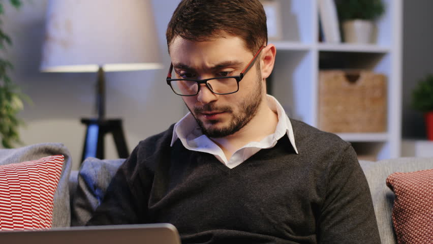 Portrait shot of the attractive man in glasses working online at his laptop computer with serious face on the sofa at home. Close up. Indoors | Shutterstock HD Video #33770089