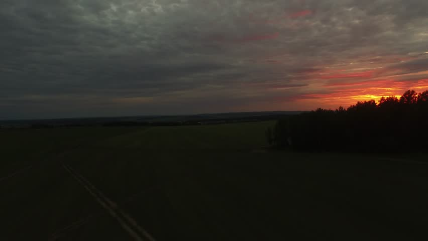 Beautiful field at sunset, aerial view. Footage. Majestic sunset in the nature landscape. Summer nature landscape. Dramatic cloudy sky