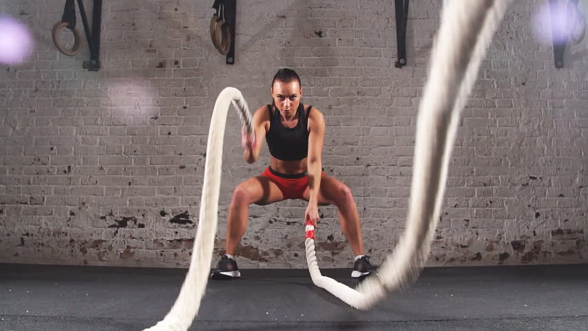 Athletic Female Actively in a Gym Exercises with Battle Ropes During Her Cross Fitness Workout. Slow motion | Shutterstock HD Video #33774547