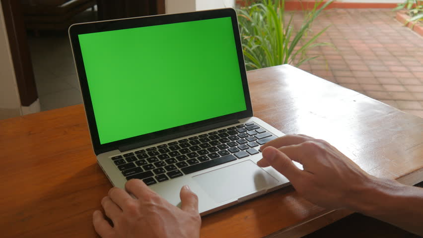 Man works at laptop at home with Green Screen. Freelancer works at home. | Shutterstock HD Video #33780013