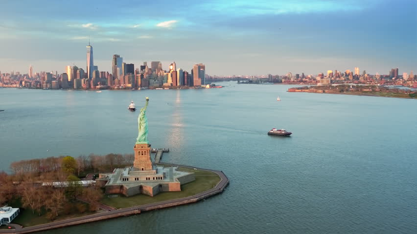 Aerial view of the Statue of Liberty at sunset. Manhattan and New Jersey skyline in the background. New York City, United States. Shot from a helicopter. | Shutterstock HD Video #33800830