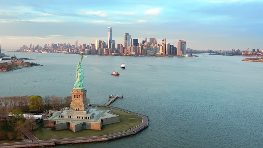 Aerial view of the Statue of Liberty at sunset. Manhattan and New Jersey skyline in the background. New York City, United States. Shot from a helicopter. | Shutterstock HD Video #33800842